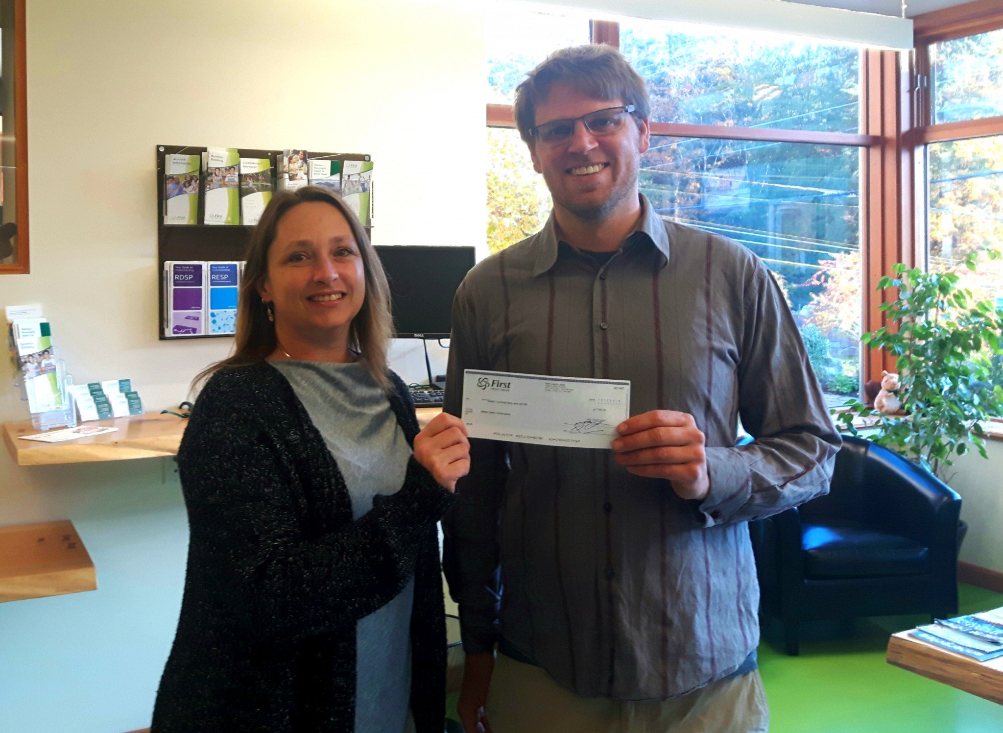 Adrian van Lidth de Jeude (our Treasurer) receives a donation cheque from First Credit Union